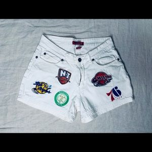 White vintage shorts with sport logos on it.
